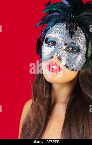 Beautiful brunette woman wearing a masqurade mask against a red background. - Stock Photo