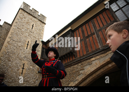 A Beefeater tells the tales of the Tower of London to visiting tourists. The first and so far only female Beefeater, - Stock Photo