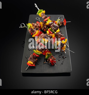 Beef and vegetable kebabs on skewers, on a black background. - Stock Photo