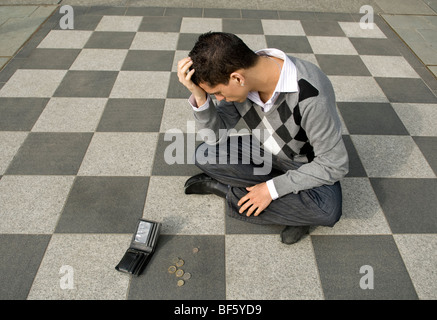A young man with his wallet on chequered concrete floor, money spilling out, head in hand, looking stressed and - Stock Photo