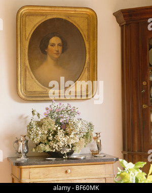 Close-up of gilt-framed portrait above flower arrangement on small chest-of-drawers - Stock Photo