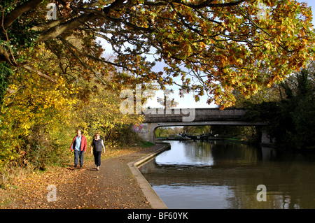 Couple walking along canal towpath in autumn, Hatton Locks, Grand Union Canal, Warwickshire, England, UK - Stock Photo