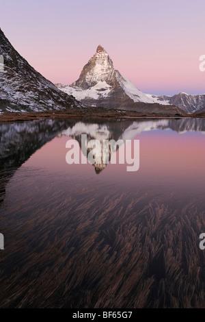 Matterhorn at sunrise in winter with reflection in the Riffelsee, Zermatt, Valais, Switzerland, Europe - Stock Photo