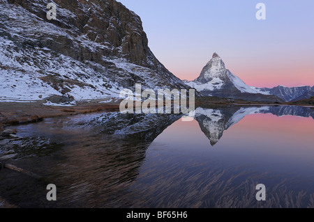 Matterhorn at sunrise in winter with reflection in the Riffelsee, Zermatt, Valais, Switzerland, Europe - Stock Photo