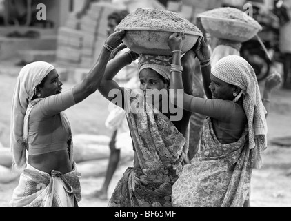 indian women working on the roads, lifting and carrying sand in a bowl on their heads. Puttaparthi, Andhra Pradesh, - Stock Photo