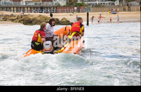 A woman is rescued from a boat by RNLI lifeguards, to be put ashore at Sandbanks, Poole, Dorset. UK. - Stock Photo