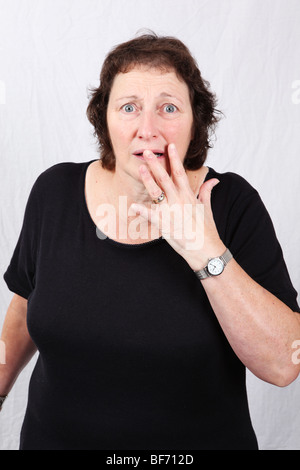 Surprised and shocked looking 50s 60s late middle aged woman aghast with hand over mouth in amazement - Stock Photo