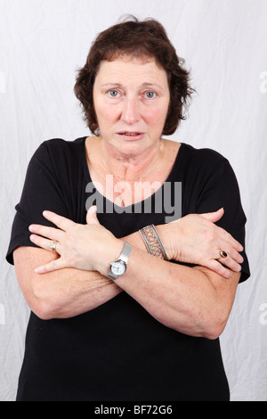 Middle aged 50s 60s woman shivering from cold sickness illness loss of body heat feeling the cold - Stock Photo