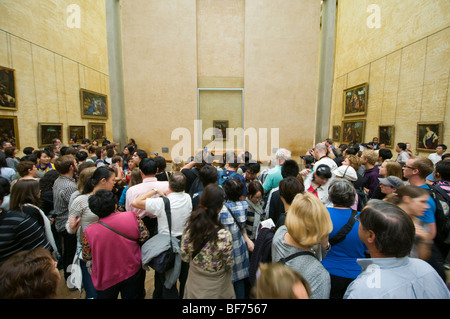 The Mona Lisa by  Leonardo da Vinci on display at the Louvre in Paris. Hundreds of people gathered around to see - Stock Photo