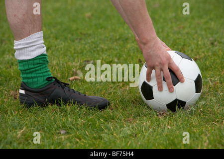 soccer football player placing the ball down for a kick - Stock Photo