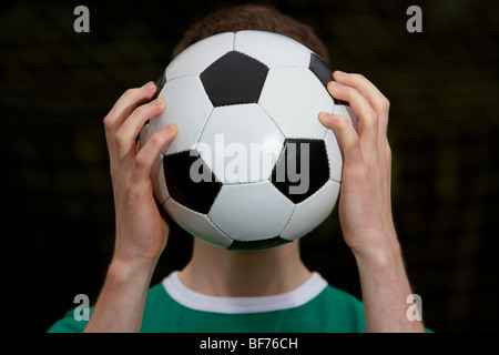soccer football player holding ball in front of his face - Stock Photo