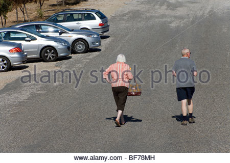 elderly couple walking to there car - Stock Photo