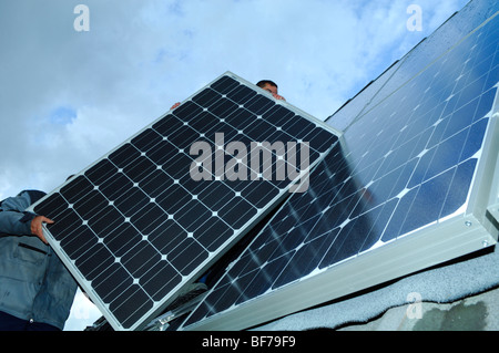 workmen installing photovoltaic solar panels on the roof of a private house - Stock Photo