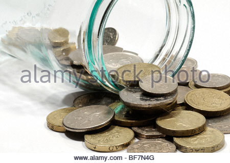 Saving small change in a jam jar, England, UK - Stock Photo