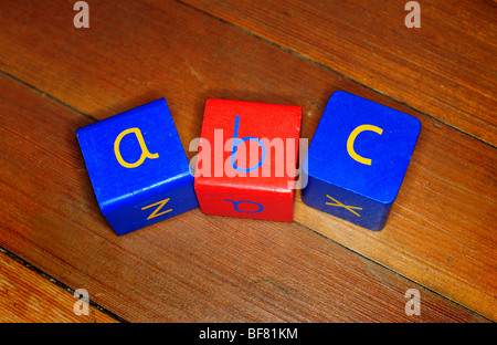 three childrens wooden blocks with a b c written on them, on a wooden floor in a nursery, to teach spelling reading - Stock Photo