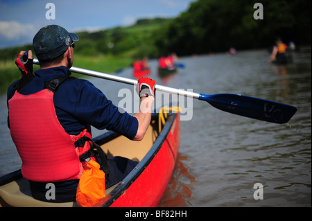 A man paddling and canoeing and kayaking on the river Tamar, on the Devon and Cornwall border, UK - Stock Photo