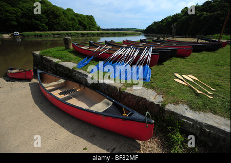 canoes and kayaks resting on the bank of the River Tamar, on the Devon and Cornwall border, UK - Stock Photo