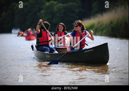 Young girls canoeing and kayaking on the river Tamar, on the Devon and Cornwall border, UK - Stock Photo