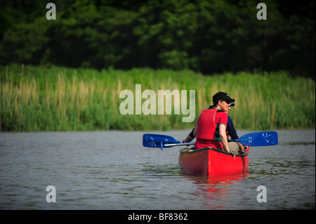 two people a man and a woman canoeing and kayaking on the river Tamar, on the Devon and Cornwall border, UK - Stock Photo