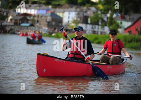 A man and a woman canoeing and kayaking on the river Tamar, on the Devon and Cornwall border, UK - Stock Photo