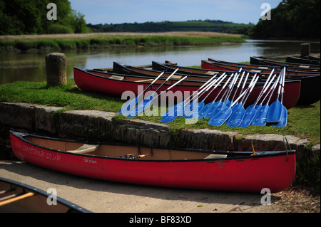 canoes resting on the bank of the River Tamar, on the Devon and Cornwall border, UK - Stock Photo