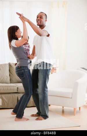 African couple and baby dancing in living room