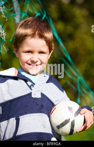 4 year old boy playing football - Stock Photo