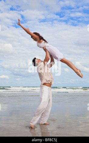 A young man holding his girlfriend above is head as she jumps in celebration on a beach - Stock Photo