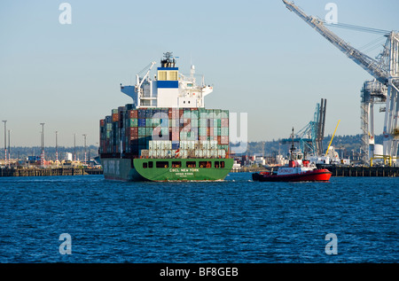 A tug boat pulls a container ship out into Elliott Bay at the Port of Seattle, Seattle, WA USA. - Stock Photo