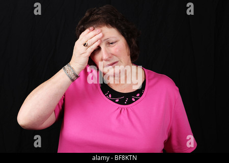 Late middle aged woman suffering from headache migraine stress holding head with hand in pain - Stock Photo