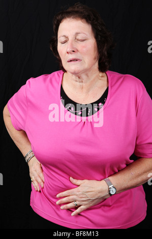 Late middle aged woman holding worn hip joint suffering severe arthritis pain requiring hip replacement procedure - Stock Photo