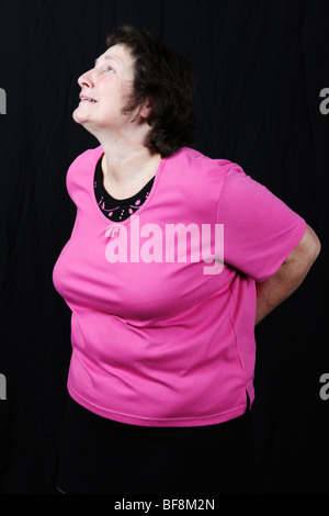 Late middle aged 50s 60s woman gripping lower back suffering severe chronic lower back pain growing old pains arthritis - Stock Photo