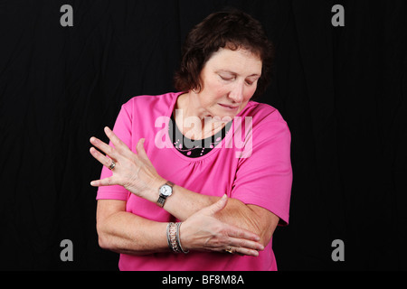 Late middle aged woman holding elbow joint suffering from severe arthritis pain tennis elbow or sports related injury - Stock Photo