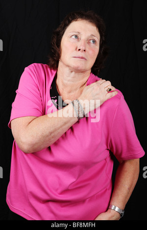 Late middle aged 50s 50s woman holds painful shoulder joint suffering from severe arthritis pain - Stock Photo