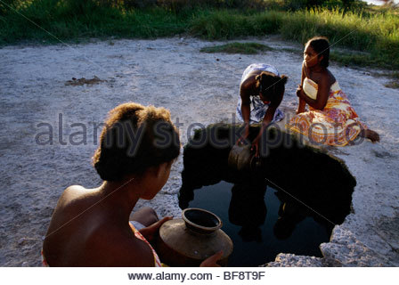 Vezo girls collecting water from underground well, Andavadaoaka, Western Madagascar - Stock Photo