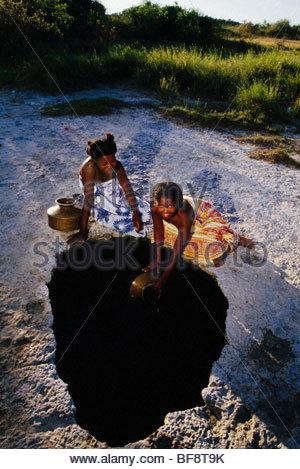 Vezo girls collecting water from underground well, Andavadaoaka, Western Madagascar - Stock Photo