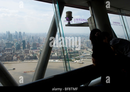 Tourists looking at Huangpu and the Bund from the Oriental Pearl Tower. Shanghai, China - Stock Photo