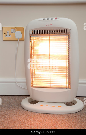 Electric halogen room heater with three heat settings plugged into electrical wall socket and switched on with high - Stock Photo
