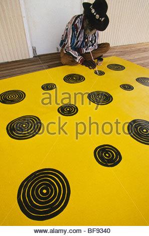 Aboriginal artist, Turkey Tolson Tjupurrula, at work, Central Desert, Australia - Stock Photo