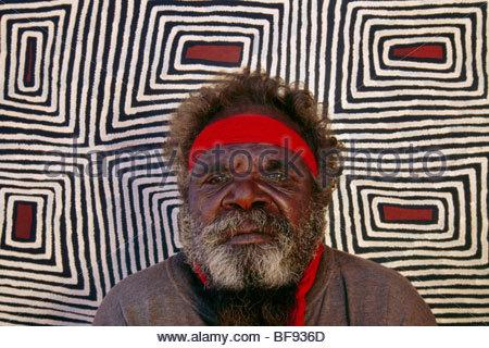 Aboriginal artist, Ronnie Tjampitjinpa, with his work, Central Desert, Australia - Stock Photo