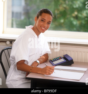 1990sw NHS consultant doing paper work and happy look at camera with pen in hand and landline phone on desk - Stock Photo