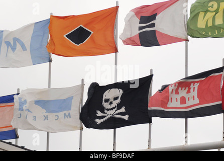 The Jolly Roger, a pirate flag, flies with the maritime flags of shipping companies at a ship-watching tourist facility - Stock Photo