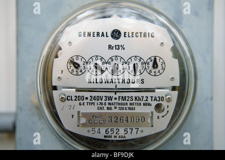 An electric meter tells a utility company how much electricity a home is using. The dials are read left-to-right - Stock Photo