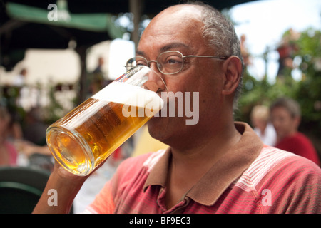 Middle aged Indian man drinking a pint of lager - Stock Photo