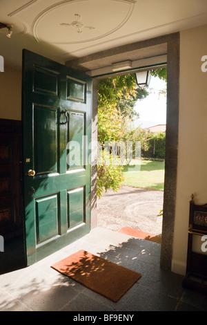 A green open door opening onto a garden on a sunny day