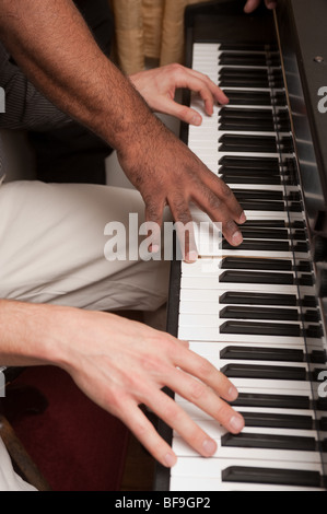 black and white hands on piano keyboard - Stock Photo