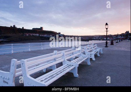 A sunset view of white benches in a line, on the west pier at the entrance to Whitby harbour, North Yorkshire. - Stock Photo