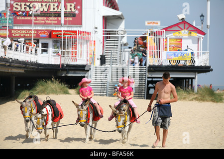 Two young girls enjoy the donkey rides on the beach beside the main pier at Great Yarmouth, Norfolk, England - Stock Photo