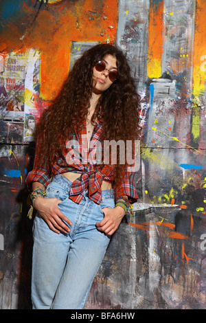 Young girl stands in front of a graffiti wall - Stock Photo