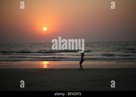 Powerkiting at sunset on the beach in Goa India - Stock Photo
